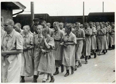 268_158Jewish women prisoners walk inside the women's camp, wearing the standard prison uniform. On the left, a SS man watches them..jpg